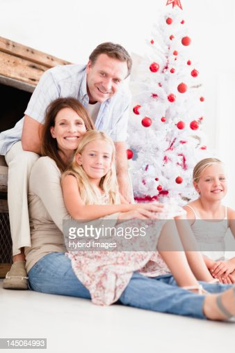 Family relaxing by Christmas tree : Stock Photo