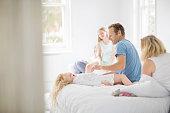 Family relaxing in bedroom