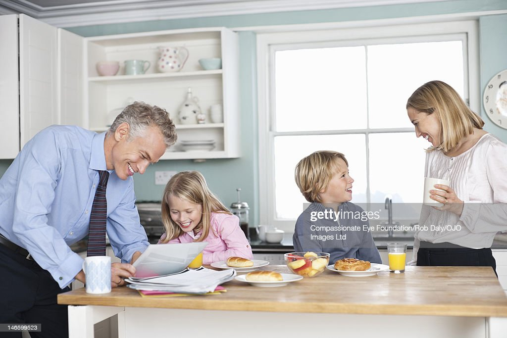 Family relaxing in kitchen with digital tablet : Stock Photo
