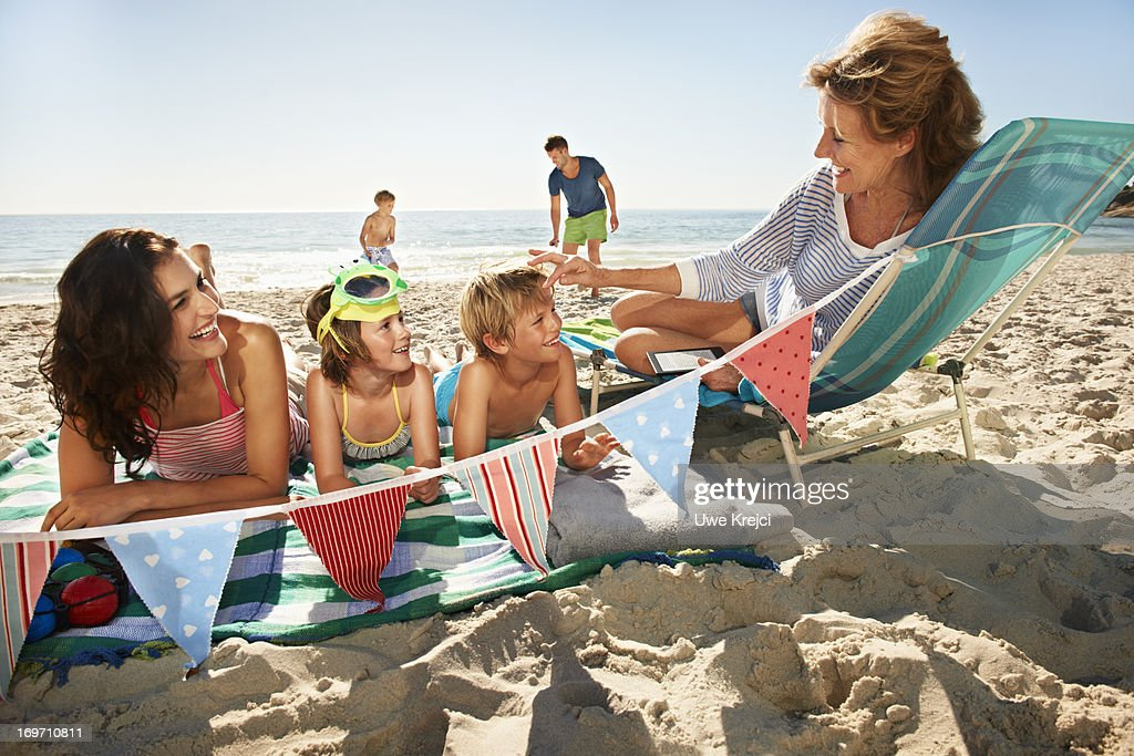 Family relaxing on beach : Stock Photo