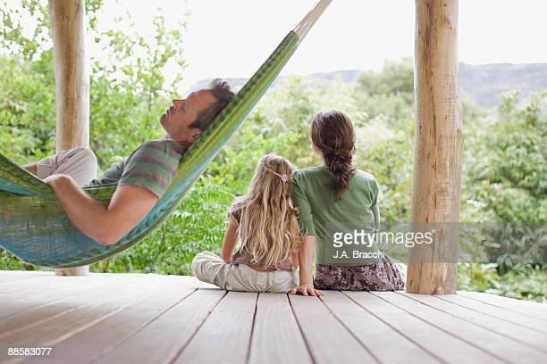 Family relaxing on porch in remote area