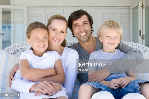 Family relaxing on sofa together : Stock Photo