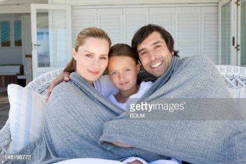 Family relaxing on sofa under blanket