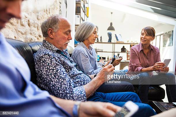 Family relaxing on the coach using smartphones