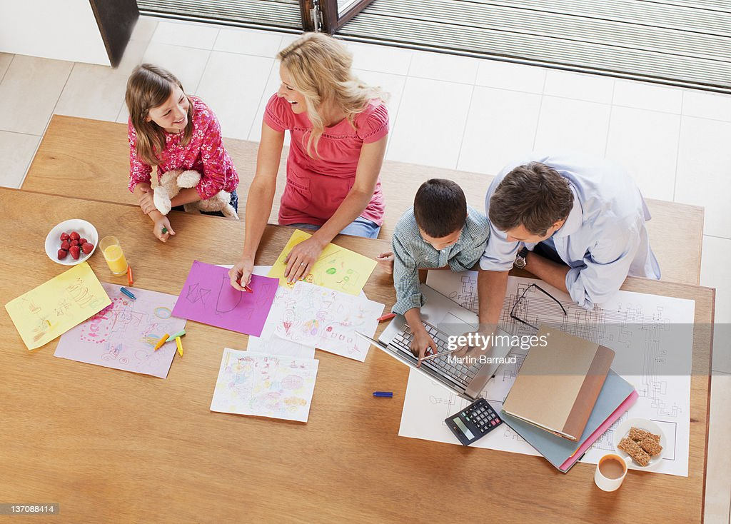 Family relaxing together at table : Stock Photo