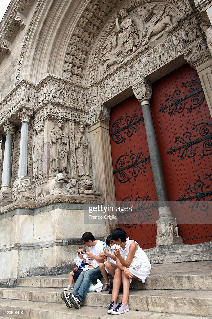 A family rest in front of the portal of Saint Trophime Church on August 11, 2012 in Arles, France. Arles is a city in the south of France in the Mouths of the Rhone. The city has a long history, and was of considerable importance in the Roman province of Gallia. The Roman Monuments of the city were listed as UNESCO World Heritage in 1981. The Dutch painter Vincent van Gogh lived in Arles in 1888-1889 and produced over 300 paintings and drawings during his time there.