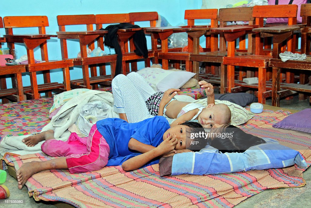 A family rest inside a classroom used as temporary shelter, after authorities evacuated residents due to Typhoon Bopha in Butuan City, Agusan del Norte, in southern island of Mindanao on December 4, 2012. Typhoon Bopha killed at least eight people in the Philippines on December 4, and there were fears the toll could rise sharply as the strongest storm to hit the country this year brought scenes of devastation. AFP PHOTO/Erwin Mascarinas