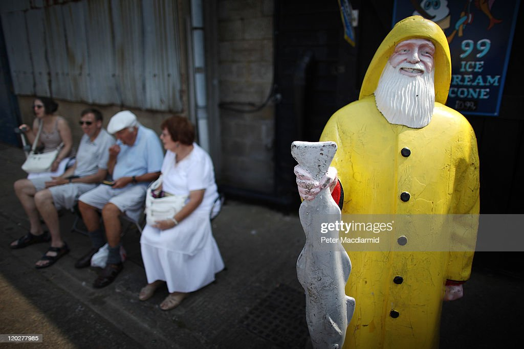 A family rest next to a fish restaurant at the harbour on August 3, 2011 in Whitstable, England. Parts of southern England are experiencing high summer temperatures.