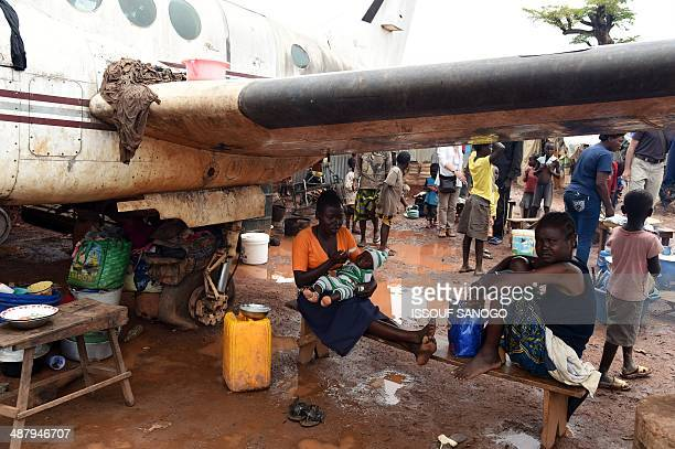 A family rest under the wing of a derelict plane on May 3 2014 in an IDP camp near Bangui's Mpoko airport where the beginning of the rain season has...