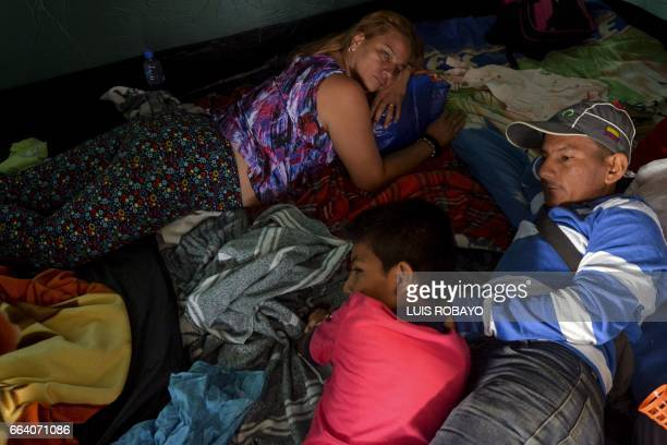 A family rests at a shelter in Mocoa Putumayo department southern Colombia on April 3 2017 Residents of Mocoa were Monday desperately searching for...