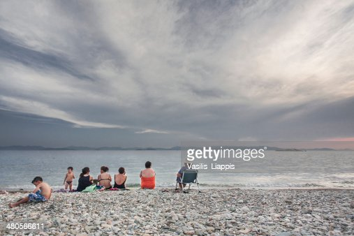 Family rests at the beach during sunset : Stock Photo