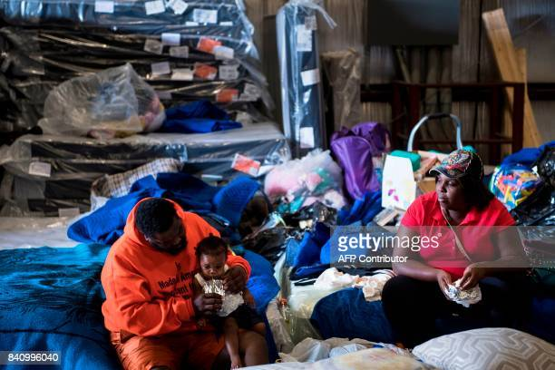 TOPSHOT A family rests in a shelter at a Gallery Furniture store during the aftermath of Hurricane Harvey on August 30 2017 in Houston Texas Monster...