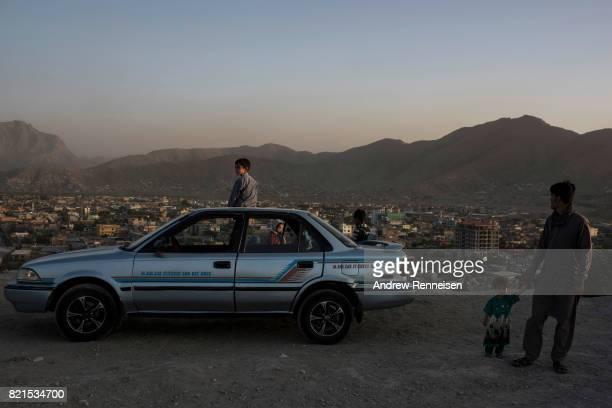 A family rests with their car in parking lot on Nader Khan Hill on July 21 2017 in Kabul Afghanistan Despite a heavy security presence throughout the...