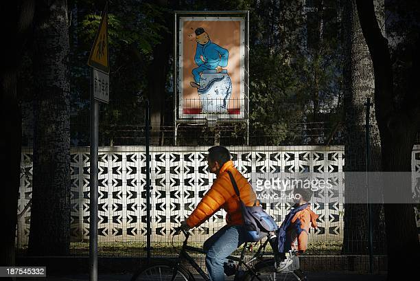 A family ride past a poster of the fictional character Tintin in Beijing on November 10 2013 Chinese state media on November 10 raised expectations...