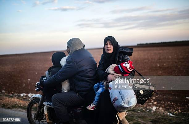 TOPSHOT A family rides a motorbike as Syrians fleeing the northern embattled city of Aleppo wait on February 5 2016 in BabAl Salama next to the city...