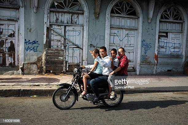 A family rides a motorcycle down the malecon during festivities to mark the Dominican Republic's 168th anniversary of its independence from Haitian...