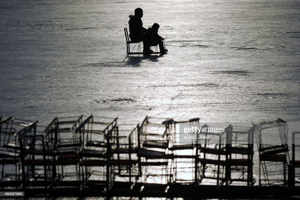 A family rides a sled on a frozen lake in Beijing on January 2, 2014. Beijing's lakes attracts scores of tourists and locals who use its frozen surface for skating and ice swimming.