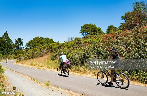 A family rides bicycles along Nimitz Way in Tilden Regional Park Berkeley California July 2016