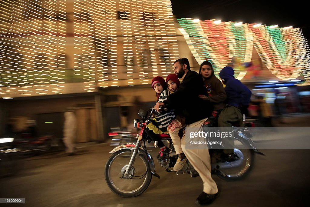 A family rides on a motor-cycle as streets and buildings are decorated with lights and ornaments within the ceremony marking the 1444th anniversary of the birthday of Prophet Mohammad, Mawlid al Nabi, in Rawalpindi, Pakistan on January 3, 2015.