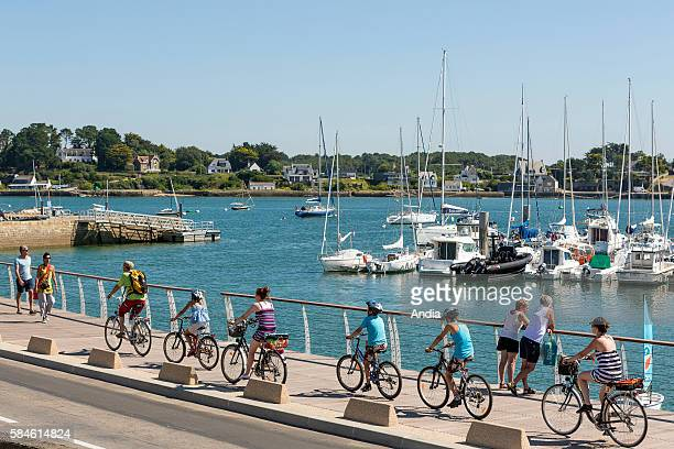 Family riding bicycles along the marina quays in La Trinite sur Mer