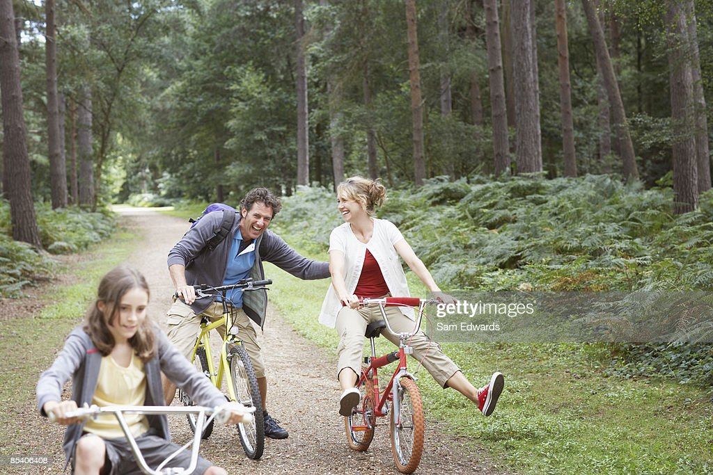 Family riding bicycles in woods : Stock Photo
