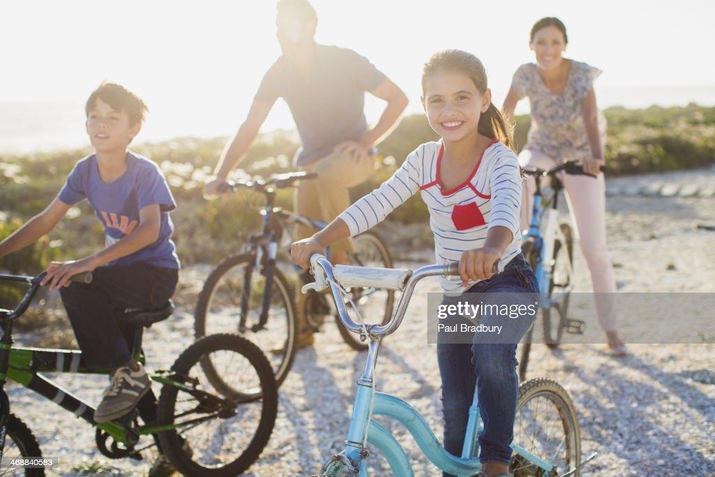 Family riding bicycles on sunny beach : Stock Photo