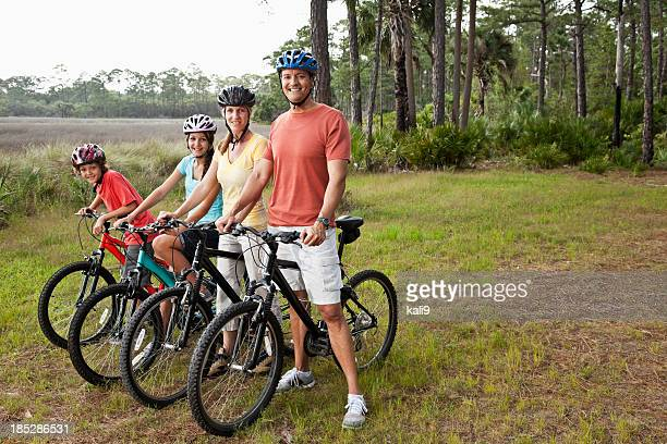 Family riding bicycles standing in a row