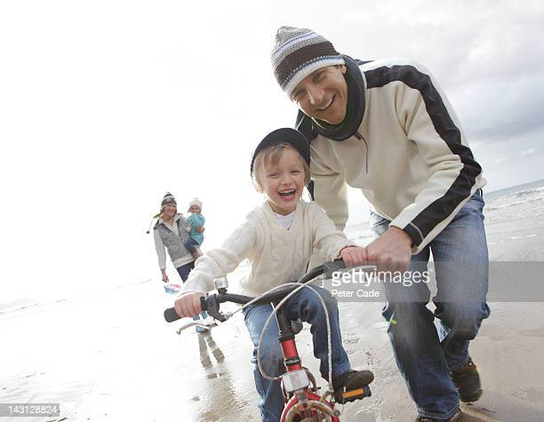 family riding bike on beach in winter