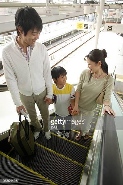 Family riding escalator at station, smiling