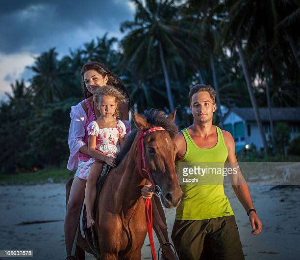 Family riding horses at sunset