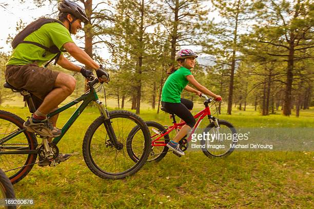 Family riding mountain bikes in meadow