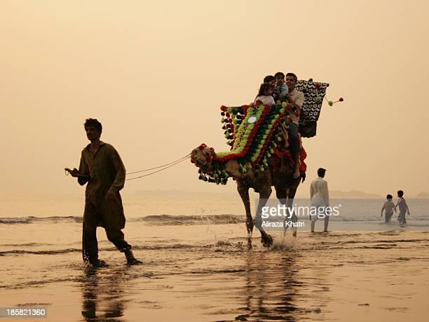 CONTENT] A family riding on a camel at the seashore of Karachi Sea view beach Pakistan