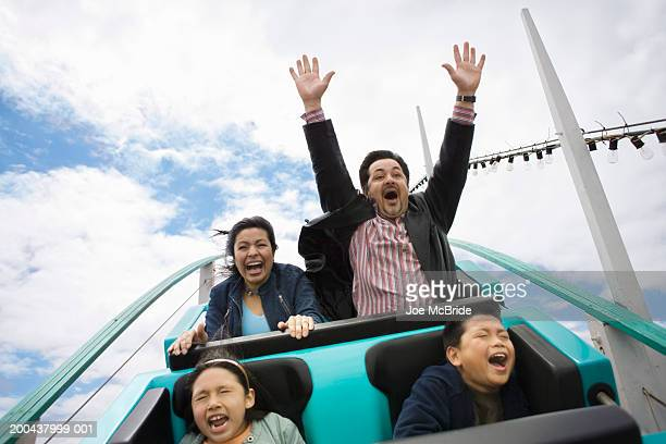 Family riding rollercoaster, father with hands up in air