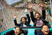 Family riding rollercoaster, parents with hands up in air