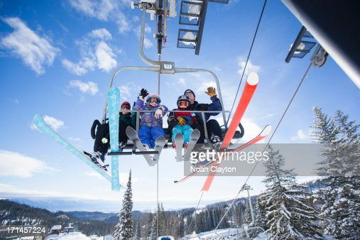 Family riding ski chairlift and waving at viewer