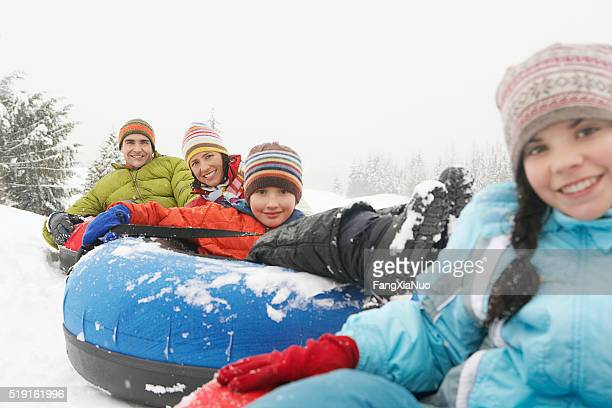 Family riding snow tubes