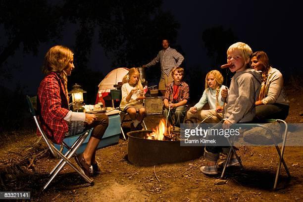 Family roasting hotdogs around campfire