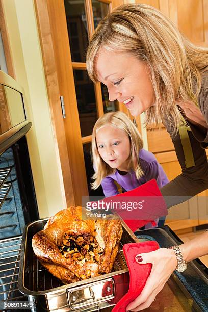 Family Roasting Thanksgiving and Christmas Turkey in Kitchen Vertical
