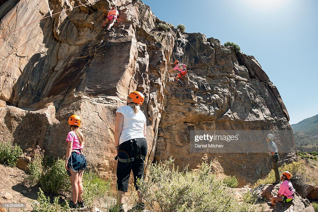 Family rock climbing with instructor. : Stock Photo