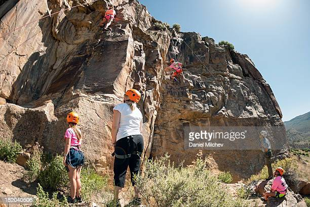 Family rock climbing with instructor.