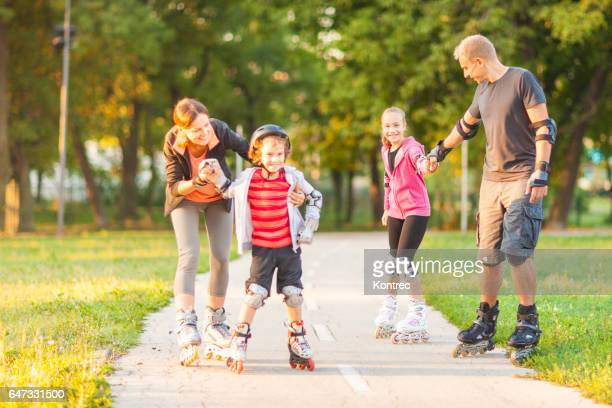 Family rollerblading in a park