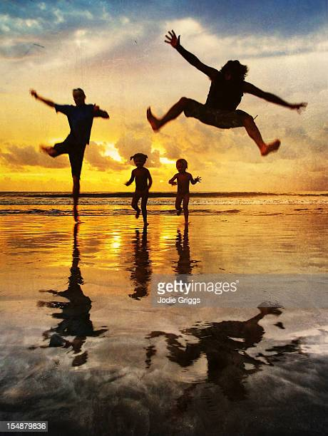 Family running and jumping at beach sunset