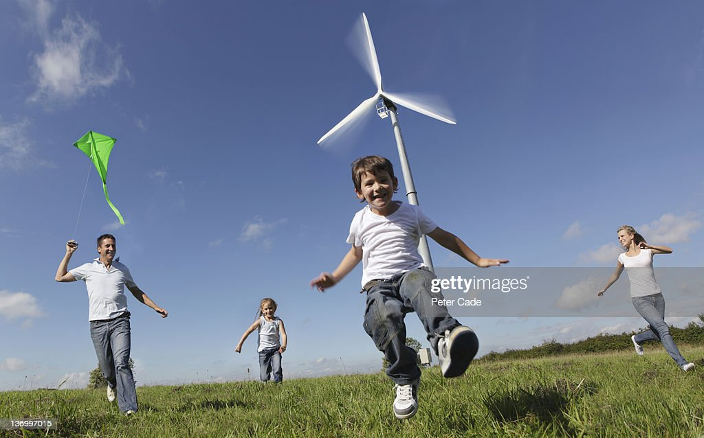 family running by wind turbine with kite : Stock Photo