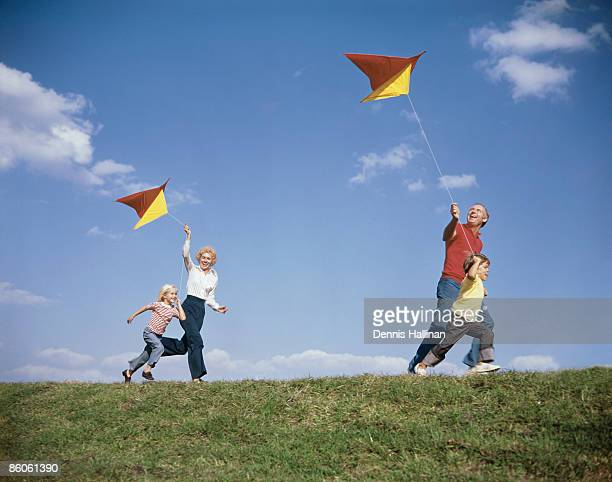Family running in park flying kites