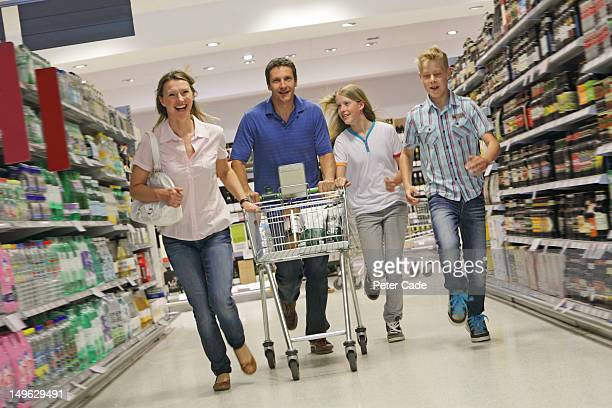 family running in supermarket aisle with trolly