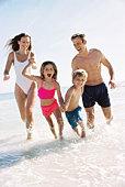 Family running in the ocean