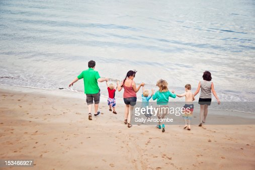 Family running into sea together : Stock Photo