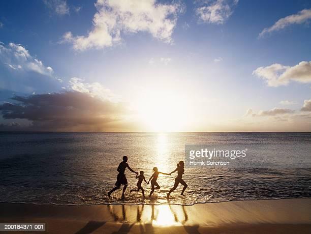 Family running on beach, holding hands, sunset