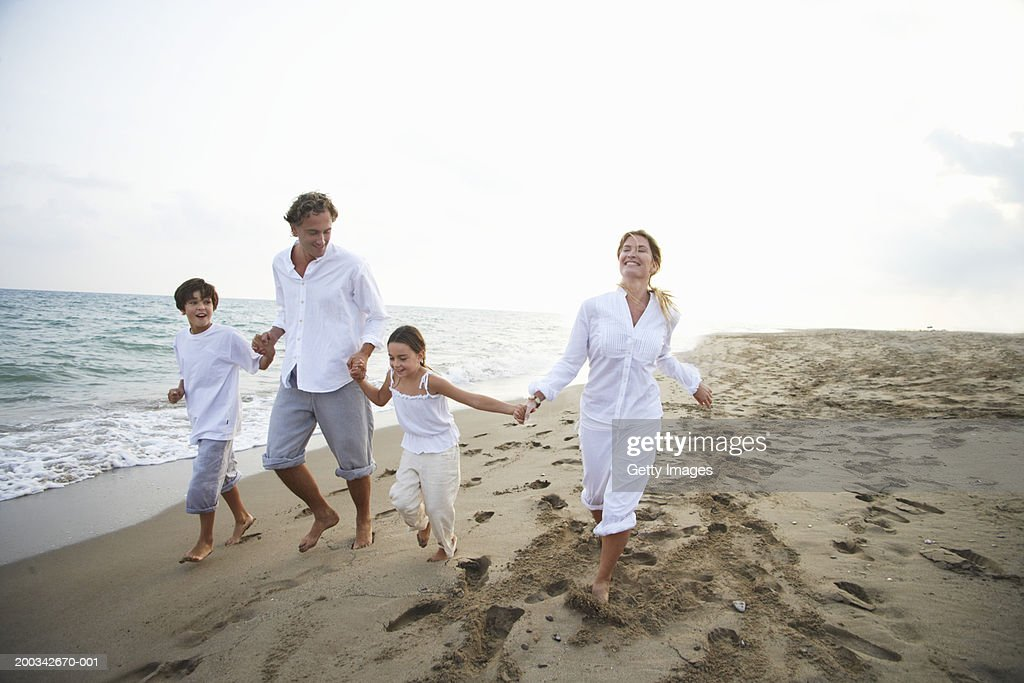 Family running on beach, parents holding children's (7-9) hands : Stock Photo
