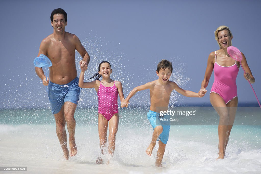 Family running on beach, smiling : Stock Photo